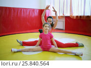Купить «Happy woman and her daughter do exercises in gym with red walls», фото № 25840564, снято 20 апреля 2015 г. (c) Losevsky Pavel / Фотобанк Лори