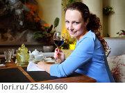 Купить «Woman smiles and holds glass with red wine in cozy restaurant», фото № 25840660, снято 12 июля 2015 г. (c) Losevsky Pavel / Фотобанк Лори