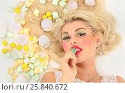 Купить «Pretty blonde woman lies among sweets and licks lollipop on floor in studio», фото № 25840672, снято 3 сентября 2015 г. (c) Losevsky Pavel / Фотобанк Лори