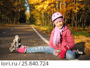 Купить «Happy girl in a protective helmet sits outstretched leg in the rollers on the asphalt in the autumn park», фото № 25840724, снято 4 октября 2014 г. (c) Losevsky Pavel / Фотобанк Лори