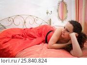 Купить «Happy pretty woman poses in long red dress lies on bed in bedroom», фото № 25840824, снято 12 июля 2015 г. (c) Losevsky Pavel / Фотобанк Лори