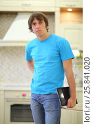 Купить «Portrait of young man in blue T-shirt with tablet computer standing in the kitchen», фото № 25841020, снято 6 октября 2014 г. (c) Losevsky Pavel / Фотобанк Лори
