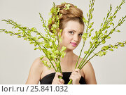 Купить «Young smiling woman in black dress holds bunches of live stems with flower buds», фото № 25841032, снято 11 января 2015 г. (c) Losevsky Pavel / Фотобанк Лори