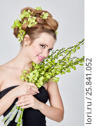 Купить «Young smiling woman in black dress holds bunch of live stems with flower buds», фото № 25841052, снято 11 января 2015 г. (c) Losevsky Pavel / Фотобанк Лори