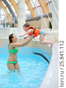 Купить «Happy little boy in a lifejacket jumping to mother in swimming pool at a waterpark», фото № 25841112, снято 28 февраля 2015 г. (c) Losevsky Pavel / Фотобанк Лори
