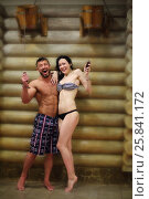 Barefoot man and a woman in a swimsuit standing under bucket-waterfall near log wall in a sauna. Стоковое фото, фотограф Losevsky Pavel / Фотобанк Лори