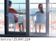 Купить «Young woman in an orange dress and daughter sitting on the balcony in the room, view through glass», фото № 25841224, снято 26 июля 2014 г. (c) Losevsky Pavel / Фотобанк Лори