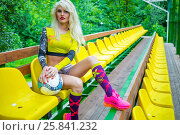 Купить «MOSCOW - JUL 16, 2015: beautiful woman (with model release) with ball in his hands in yellow top resting on bench», фото № 25841232, снято 16 июля 2015 г. (c) Losevsky Pavel / Фотобанк Лори