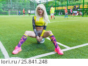 MOSCOW - JUL 16, 2015: Beautiful woman (with model release) sitting on ball at gate in top on football pitch. Редакционное фото, фотограф Losevsky Pavel / Фотобанк Лори