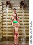 Купить «Happy woman with two boys overturns the wooden buckets with water near log wall», фото № 25841260, снято 28 февраля 2015 г. (c) Losevsky Pavel / Фотобанк Лори