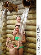 Купить «Happy woman with two boys overturns the wooden buckets with water near log wall in a sauna», фото № 25841264, снято 28 февраля 2015 г. (c) Losevsky Pavel / Фотобанк Лори