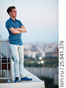 Купить «Young man in denim clothes stands crossing arms on chest on the roof leaning his back to the railing», фото № 25841376, снято 4 июня 2015 г. (c) Losevsky Pavel / Фотобанк Лори