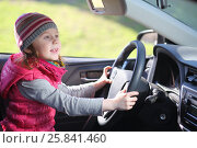 Купить «Happy little girl in pink waistcoat and striped hat sitting at wheel of car», фото № 25841460, снято 17 апреля 2014 г. (c) Losevsky Pavel / Фотобанк Лори