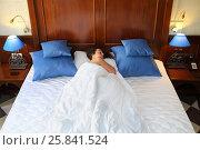 Купить «SOCHI, RUSSIA - JUL 27, 2014: Beautiful woman with curly hair (model release) is sleeping in the big bed in the Hotel Bogatyr, top view», фото № 25841524, снято 27 июля 2014 г. (c) Losevsky Pavel / Фотобанк Лори