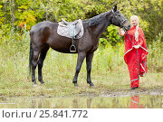 Купить «Blonde woman with plait in red clothes stands with horse in park near water», фото № 25841772, снято 13 сентября 2015 г. (c) Losevsky Pavel / Фотобанк Лори
