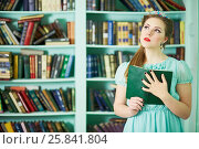 Купить «Young woman in green dress stands at library holding book», фото № 25841804, снято 7 марта 2015 г. (c) Losevsky Pavel / Фотобанк Лори