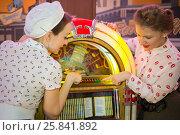 Купить «Two girls in retro dress press button on old-fashion musical mac», фото № 25841892, снято 18 января 2015 г. (c) Losevsky Pavel / Фотобанк Лори