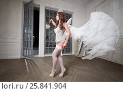 Young woman in white underwear, stockings and angel wings behind her back walks along room. Стоковое фото, фотограф Losevsky Pavel / Фотобанк Лори