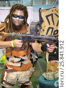 Купить «MOSCOW - OCT 12, 2014: Cosplayer with dreadlocks and wearing glasses with a gun in his hand at the EveryCon 2014 in the exhibition center Sokolniki», фото № 25841912, снято 12 октября 2014 г. (c) Losevsky Pavel / Фотобанк Лори
