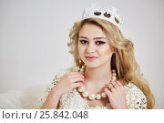 Купить «Young smiling blond woman in crown touches beads of big artificial pearls on her neck», фото № 25842048, снято 7 марта 2015 г. (c) Losevsky Pavel / Фотобанк Лори