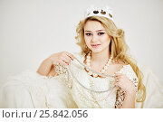 Купить «Young smiling blond woman in crown on head holds beads of pearls», фото № 25842056, снято 7 марта 2015 г. (c) Losevsky Pavel / Фотобанк Лори