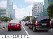 Купить «Many cars move on city road amonf tall buildings in Shanghai, China», фото № 25842112, снято 5 ноября 2015 г. (c) Losevsky Pavel / Фотобанк Лори