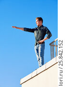 Купить «Young man in denim wear stands on the edge of the building roof outstretching one arm in front of him», фото № 25842152, снято 12 июня 2015 г. (c) Losevsky Pavel / Фотобанк Лори