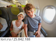 Купить «Girl and boy sit in armchairs at airplane», фото № 25842188, снято 8 августа 2016 г. (c) Losevsky Pavel / Фотобанк Лори