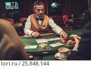 Купить «Croupier behind gambling table in a casino», фото № 25848144, снято 19 марта 2018 г. (c) Andrejs Pidjass / Фотобанк Лори