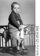 Купить «Маленький советский ребёнок сидит на игрушечной деревянной лошадке», эксклюзивное фото № 25854968, снято 7 декабря 2019 г. (c) Максим Мицун / Фотобанк Лори