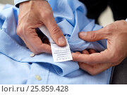 Купить «hands with shirt and care instruction label», фото № 25859428, снято 13 ноября 2014 г. (c) Syda Productions / Фотобанк Лори