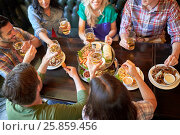 Купить «happy friends eating and drinking at bar or pub», фото № 25859456, снято 14 июля 2016 г. (c) Syda Productions / Фотобанк Лори