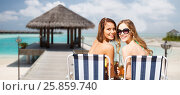 Купить «happy young women with drinks sunbathing on beach», фото № 25859740, снято 11 июля 2013 г. (c) Syda Productions / Фотобанк Лори