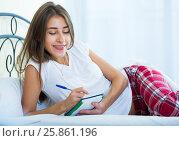 Купить «Smiling girl making shopping list in bedroom», фото № 25861196, снято 23 февраля 2019 г. (c) Яков Филимонов / Фотобанк Лори