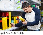 Купить «Young positive man choosing insects killer spray», фото № 25861456, снято 19 октября 2018 г. (c) Яков Филимонов / Фотобанк Лори