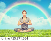 woman meditating in lotus yoga pose over rainbow. Стоковое фото, фотограф Syda Productions / Фотобанк Лори