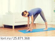 Купить «woman making yoga intense stretch pose on mat», фото № 25871368, снято 13 ноября 2015 г. (c) Syda Productions / Фотобанк Лори