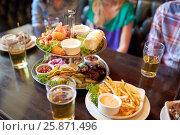 Купить «people sitting at table with food and beer at bar», фото № 25871496, снято 14 июля 2016 г. (c) Syda Productions / Фотобанк Лори