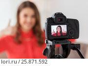 Купить «woman with camera recording video at home», фото № 25871592, снято 22 декабря 2016 г. (c) Syda Productions / Фотобанк Лори