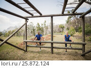 Купить «Fit man and woman climbing monkey bars during obstacle course», фото № 25872124, снято 24 ноября 2016 г. (c) Wavebreak Media / Фотобанк Лори