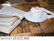 Купить «Coffee cup by open book on table in cafeteria», фото № 25872408, снято 12 октября 2016 г. (c) Wavebreak Media / Фотобанк Лори