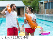 Купить «Lifeguards holding rescue cans at poolside», фото № 25873448, снято 12 декабря 2016 г. (c) Wavebreak Media / Фотобанк Лори