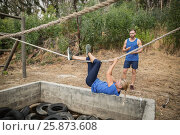 Купить «Woman climbing rope during obstacle course training», фото № 25873608, снято 24 ноября 2016 г. (c) Wavebreak Media / Фотобанк Лори