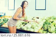Купить «Glad female customer holding fresh cabbage-head», фото № 25881616, снято 14 ноября 2018 г. (c) Яков Филимонов / Фотобанк Лори