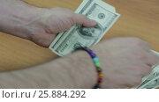 Купить «Мужские руки с браслетом считают стодолларовые банкноты», видеоролик № 25884292, снято 3 апреля 2017 г. (c) Круглов Олег / Фотобанк Лори