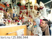Купить «Happy family choosing Christmas decoration at Christmas market», фото № 25886944, снято 17 июля 2019 г. (c) Яков Филимонов / Фотобанк Лори
