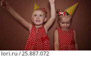 Купить «Two charming little sisters twins in holiday caps with sparkling Bengal lights in their hands having fun on a holiday», видеоролик № 25887072, снято 12 января 2017 г. (c) Mikhail Davidovich / Фотобанк Лори