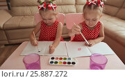 Купить «Two little sisters twins are happy to paint drawings with watercolors sitting at the table together», видеоролик № 25887272, снято 12 января 2017 г. (c) Mikhail Davidovich / Фотобанк Лори