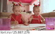 Купить «Two little sisters twins are happy to paint drawings with watercolors sitting at the table together», видеоролик № 25887276, снято 12 января 2017 г. (c) Mikhail Davidovich / Фотобанк Лори