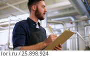 Купить «men with clipboard at brewery or beer plant», видеоролик № 25898924, снято 23 мая 2019 г. (c) Syda Productions / Фотобанк Лори